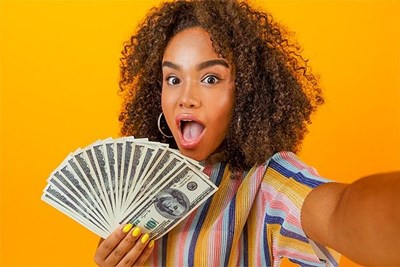 A girl on an orange background holds up several $100 bills to the camera