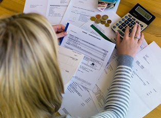 a woman calculating finances on a calculator with multiple bills spread out in front of her