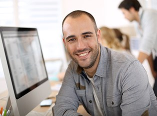 Man looking away from a computer where he is researching his new business idea