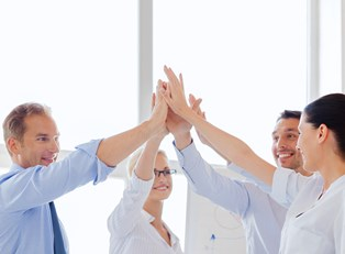 Business associates high five after finding success starting a business using the right advice