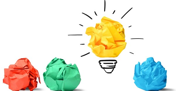 Wads of red, green, and blue paper lying next to a yellow wad of paper turned into a light bulb representing a brilliant business idea