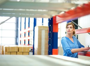 Woman conducts inventory management in a large warehouse to save money
