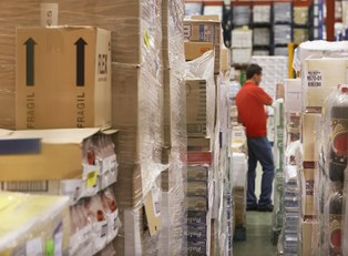 Man checking the information provided in inventory management software against the inventory in the warehouse.