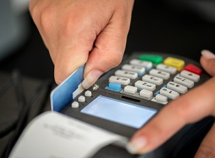 A small business owners swipes a credit card using credit card processing equipment.