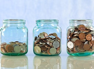 Three jars holding spare change to represent how small things add up to big savings.