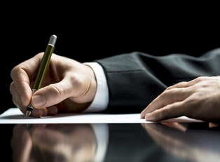 Man in a suit signing for a certificate deposit after reviewing the advantages and disadvantages.