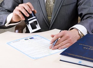 Man stamping a certificate of deposit agreement after the investor has managed his account and decided to get a new interest rate.
