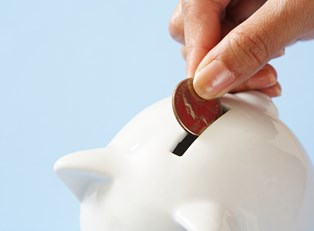 Woman's hand placing a penny into a white piggy bank to save money rather than risk the repercussions of not being able to repay a guarantor loan.
