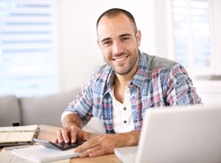 Man smiling as he checks on his online savings account from his computer at home.