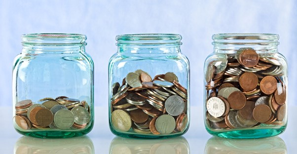Three jars filled with varying amounts of coins to represent the three kinds of savings accounts.