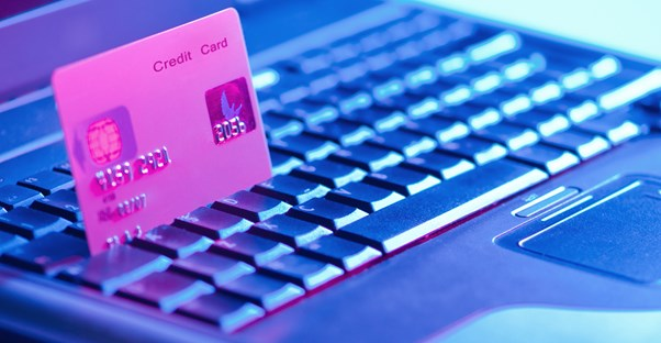 A credit card sitting between the keys of a laptop as someone researches for the advantages of consolidating credit cards.