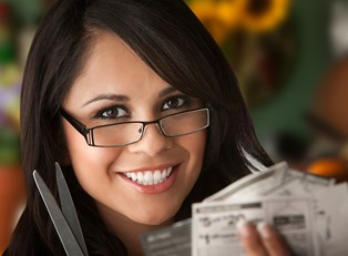 Woman smiling as she clips coupons like a normal person.