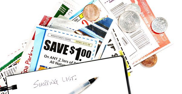 A pile of coupons and coins and a pen laying on table after a woman started couponing.