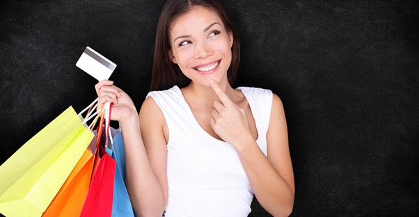Young woman holds shopping bags and smiles guiltily after making several impulse purchases with her credit card.