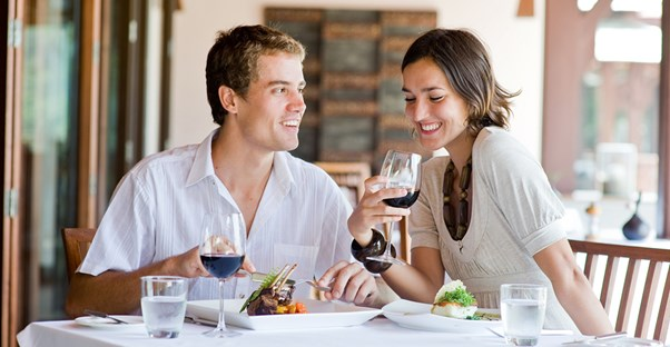 A young couple smiles while they eat dinner because they saved money with coupons and specials.