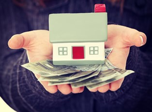 Woman holding a toy house and a fan of dollars bills in the palms of her hands to represent how home loans work.