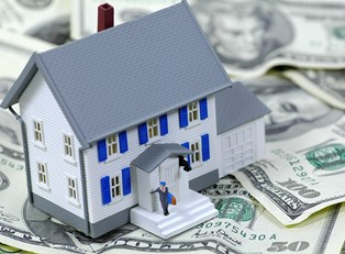 A plastic toy house sitting on a pile of money to represent how you qualify for a home loan.
