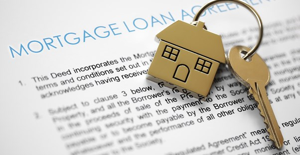 A gold key on a gold house key chain laying on top of a home loan program agreement.