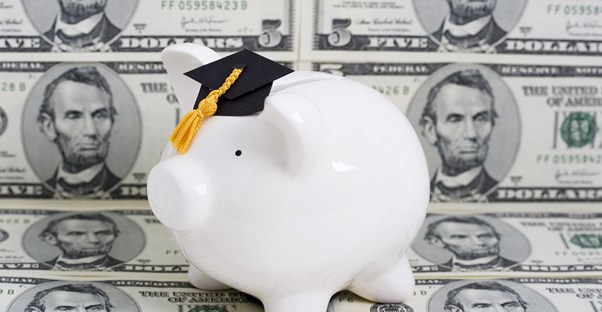 A piggy bank wearing a graduation hat in front of money that was received through financial aid.