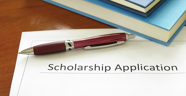 After researching financial aid options, a future college student leaves a scholarship application sitting on a desk with a pen and stack of books.