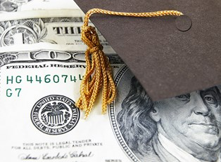 A college graduation cap resting on a hundred dollar bill obtained through financial aid.