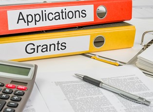 Folders for grants and applications piled on a desk next to other documents need to qualify for the Pell Grant and it's advantages.