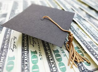 A graduation cap on a stack of money earned through college scholarships.