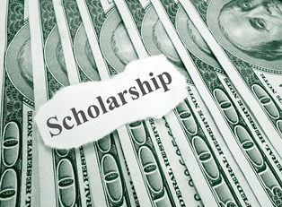A piece of paper saying SCHOLARSHIP laying on top of money earned by finding available college scholarships.