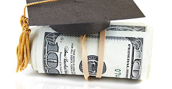 A miniature graduation cap sitting on top of a roll of money received from college scholarships.