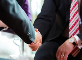 A client and financial adviser shaking hands after discussing the advantages of having a financial adviser.