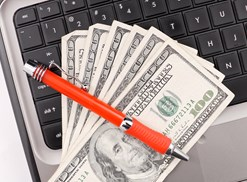 Money on a laptop with a pen across it