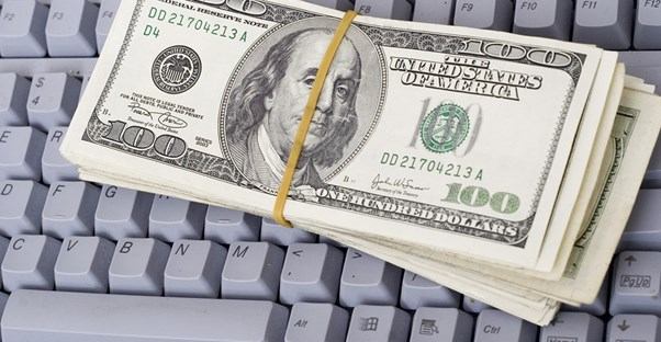 Bundle of 100 dollar bills on a keyboard
