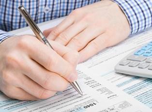 Man in Plaid Shirt Signing Paperwork