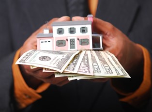 Man holding a house and cash from a low interest home equity loan