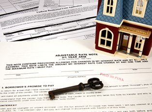 Miniature home and key on top of home equity loan paperwork