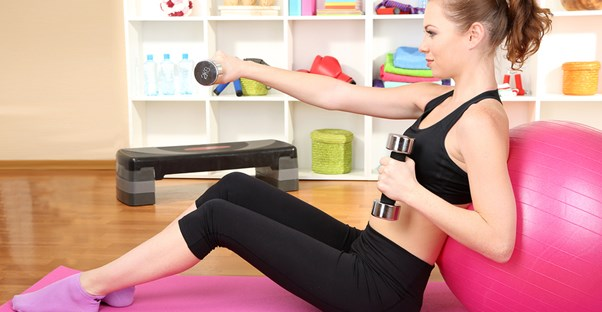 Woman working out in a home gym with expensive equipment