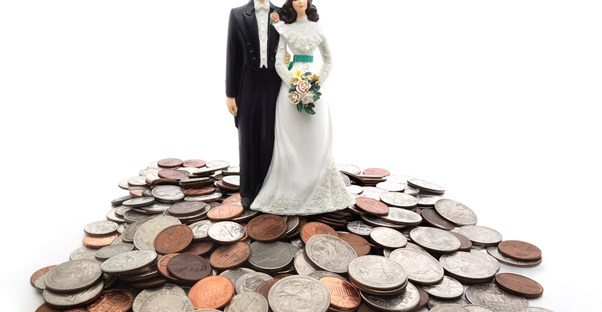 Wedding cake topper on top of a pile of coins