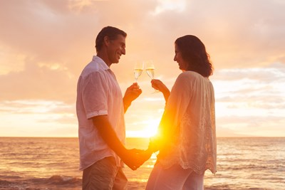 A retired couple is standing on the beach with glasses of champagne