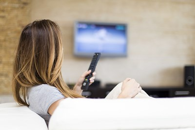 woman watching cable tv on a tv mounted to her wall