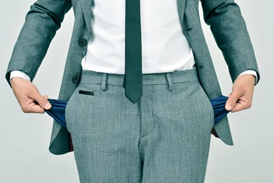 Man in a suit holding out his empty pockets