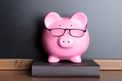 Nerdy piggy bank sitting on a book on a shelf
