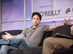 Sergey Brin sitting in a chair at a conference